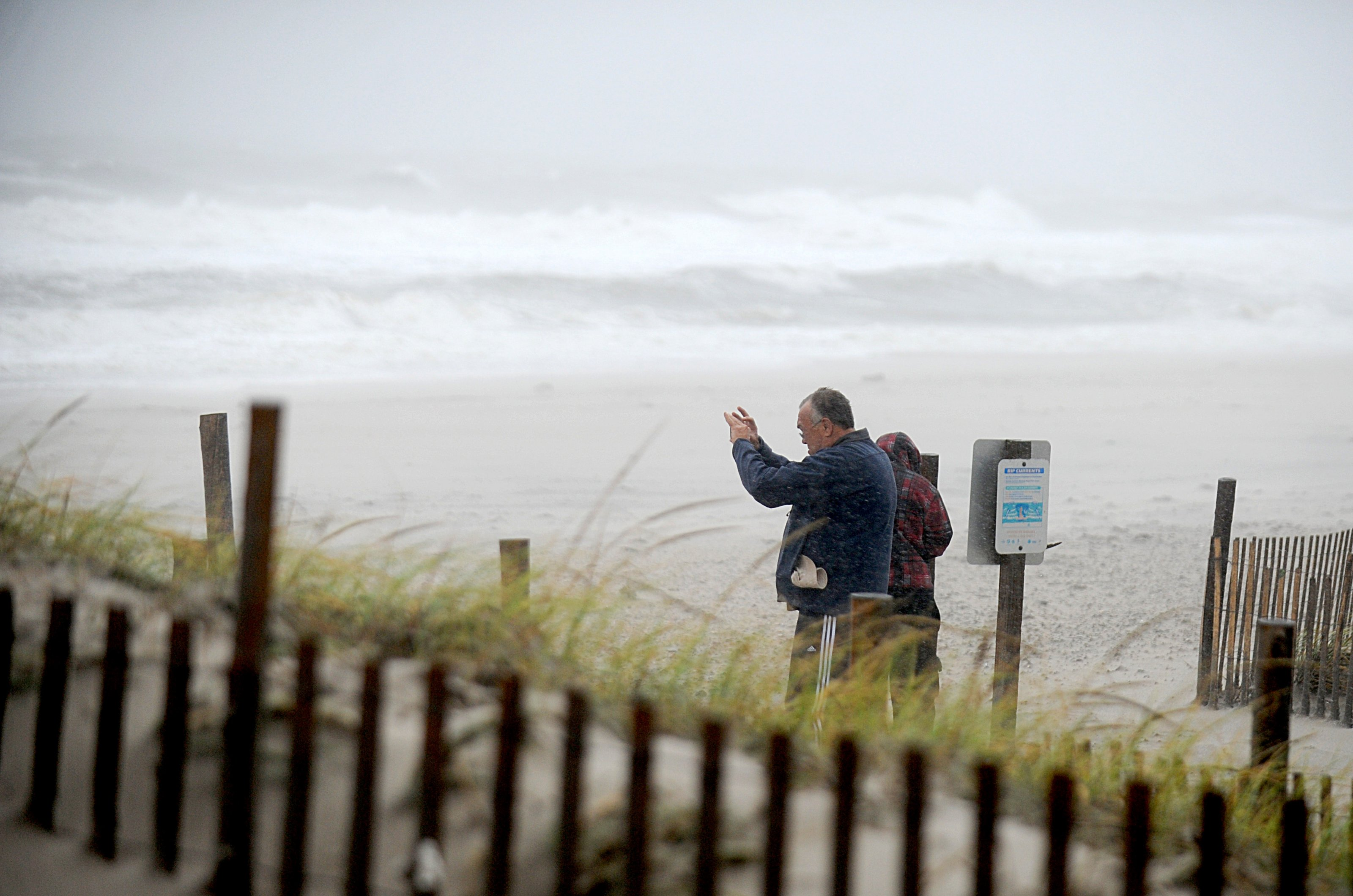 A man stands on the beach and takes photos of high waves and rough waters as they hit the shore line when rain and wind from Hurricane Joaquin arrives on the east coast of the United States on October 2, 2015 in Seaside Heights, NJ. The flooding scenario will develop Friday night and through the weekend as flash flood watches extend from Atlanta to near New York City. Photo by Dennis Van Tine/ABACAPRESS.COM